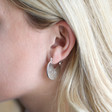 Brushed Silver Triangle Cut Out Hoop Earrings on Model