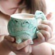 Lisa Angel with Ceramic House of Disaster Diplodocus Cup