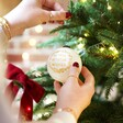 Model Holding Hand-Painted Gold Wreath Bauble