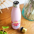 house of disaster pink beatles bottle with lid off on textured table