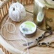 Tin of Hedgehog Mix Seed Balls Amongst String and Scissors On A Table