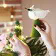 Model Putting Dove Felt Tree Topper on Tree