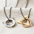 silver and golds men's personalised double geometric charm necklaces laid on hessian background