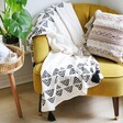 Black and White Sass & Belle Triangle Block Print Throw Blanket Draped over Armchair