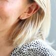Model Wearing Tiny Stainless Steel Heart Stud Earrings in Gold