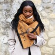 Model Wearing Personalised Embroidered Check Blanket Scarf in Light Brown  with one hand on scarf and looking down