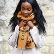 Model Wears Lisa Angel Personalised Embroidered Check Blanket Scarf in Light Brown