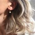 Model Wearing Lisa Angel Daisy Charm Huggie Hoop Earrings in Gold