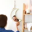 Lisa Angel Gold Moon Wall Mirror hanging on the wall