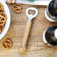 oak bottle opener from lisa angel on table with pretzels and beer bottles