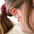 Red Enamel Heart Charm Huggie Hoop Earrings on Model
