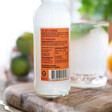 ingredients list on back of artisan drinks co fiery ginger beer next to glass with lime