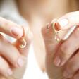 Model Holding Lisa Angel Crystal Moon Huggie Hoop Earrings in Gold