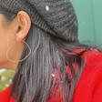 Model Wearing Lisa Angel Ladies' Sparkle Cut Heart Hoop Earrings in Silver