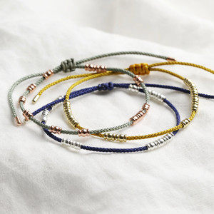 Mustard cord bracelet with sweet bead and end stoppers in gold