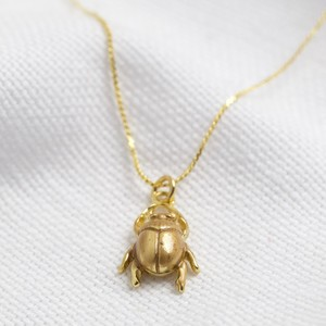Worn gold bug necklace